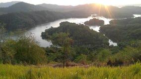 El lago y la montaña en bosque con el sol suben foto de archivo libre de regalías