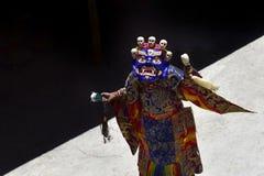 El lama con los brazos abiertos en ropa monástica festiva realiza danza de la máscara en el monasterio budista de Karcha, Zanskar Foto de archivo