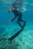 El lanza-pescador de sexo femenino recarga el arma sobre el filón coralino Foto de archivo libre de regalías