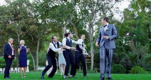 El lanzamiento de la liga del novio feliz y los padrinos de boda lo cogen 4K 4k metrajes