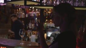 El lanzamiento de la muchacha en gente del teléfono en la barra se coloca en partido en club nocturno holidays Sonrisa almacen de video
