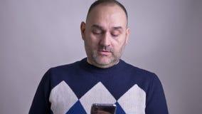 El lanzamiento del primer del centro envejeció mandar un SMS masculino caucásico en el teléfono y la sonrisa con el fondo aislado almacen de video