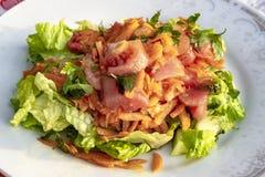 El lanzamiento para la zanahoria, el tomate y el follaje mezclan la ensalada caída aceite en la placa blanca fotografía de archivo libre de regalías
