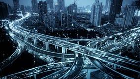 El lapso de tiempo, semáforos se arrastra y los vehículos en el paso superior intercambian en la noche almacen de metraje de vídeo