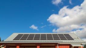 El lapso de tiempo ultra alto de la definición de nubes blancas de mudanza y del cielo azul sobre tejado con los paneles solares  almacen de metraje de vídeo