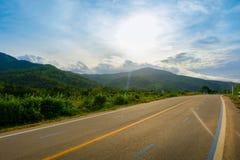 El largo camino pasa a través de las montañas y del cielo azul Imagen de archivo libre de regalías