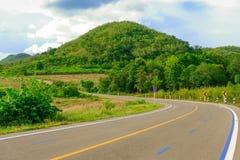 El largo camino pasa a través de las montañas y del cielo azul el día de fiesta Fotografía de archivo
