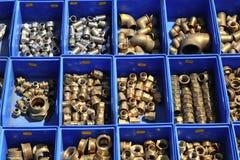 El latón de bronce de la plomería junta las piezas de los rectángulos azules Imágenes de archivo libres de regalías