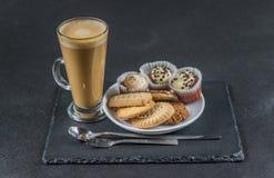 El latte aromático del café con tres untó con mantequilla los molletes y el pastelito imagen de archivo libre de regalías