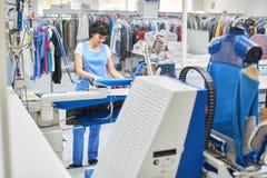 El lavadero del trabajador planchado viste el hierro seco imagen de archivo libre de regalías
