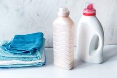 El lavadero fijó con las toallas y los bottels del plástico en el fondo blanco imagenes de archivo