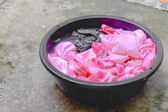 El lavarse empapa la ropa sucia en el negro del lavabo para limpia Imágenes de archivo libres de regalías