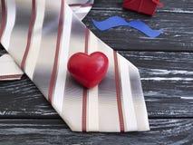 El lazo, corazón, bigote de papel, idea romántica celebra la caja de regalo de los presentes en un viejo fondo de madera negro Imagen de archivo libre de regalías