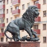 El león de la escultura presiona la serpiente Foto de archivo