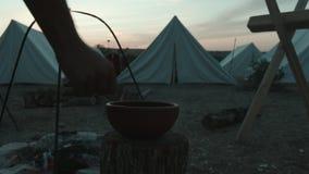 El legionario romano saca el agua con pala de un jarro en el campo militar almacen de metraje de vídeo