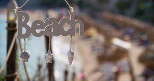 El letrero de madera cuelga contra el océano almacen de video