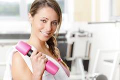El levantamiento de pesas sonriente de la mujer joven en el gimnasio y la mirada vinieron Fotos de archivo