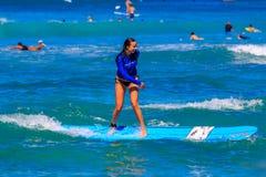 El levantarse que practica surf de la chica joven en la playa Hawaii de Waikiki Fotografía de archivo