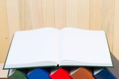 El libro abierto, pila de libro encuadernado reserva en la tabla de madera Imagenes de archivo