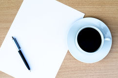 El Libro Blanco en blanco está en la tabla con la pluma y el café de bola a un lado Fotografía de archivo