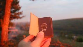 El libro con la inscripción a viajar es vivir Puesta del sol en el bosque almacen de metraje de vídeo