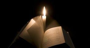 El libro de la biblia cambia las paginaciones delante de una vela fotos de archivo libres de regalías