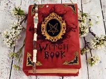 El libro de la bruja en cubierta roja con pentagram, la vara mágica y la primavera florece en la tabla Foto de archivo