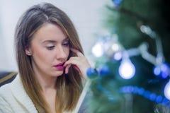 El libro de lectura de la mujer en la Navidad adornó a casa Concepto del día de fiesta, días de fiesta, ocio, literatura Fotografía de archivo