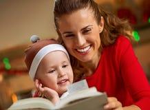 El libro de lectura de la madre y del bebé en la Navidad adornó la cocina Foto de archivo libre de regalías