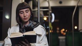 El libro de lectura de la mujer joven o del pasajero que se sentaba en el transporte público, steadicam tiró C?mara lenta La ciud almacen de video