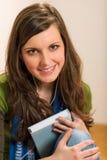 El libro del asimiento de la mujer del adolescente del estudiante escucha música Imagen de archivo libre de regalías