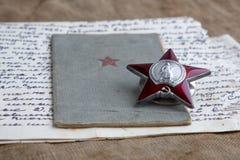 El libro del soldado, la orden de Red Star y la vieja letra en la lona Primer, la memoria de la guerra 9 de mayo fotografía de archivo libre de regalías