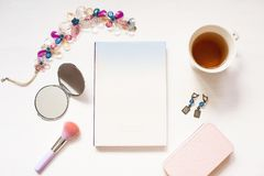 El libro en blanco aislado en blanco texturizó el fondo de madera con los accesorios lindos del ` s de las mujeres Cuaderno plano Fotos de archivo