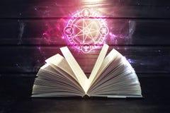 El libro en la tabla hacia fuera viene muestra ligera y mágica Imagenes de archivo