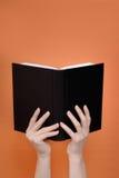El libro en manos Foto de archivo