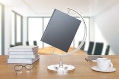 El libro es como un globo en el escritorio con los libros y la taza de café Imagenes de archivo