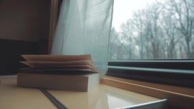 El libro est? en la tabla en el tren Viaje de tren del coche del concepto del viaje del ferrocarril visi?n hermosa de la ventana  almacen de video