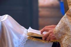 El libro está en las manos de un sacerdote imagen de archivo