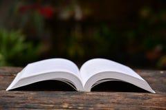 El libro puso la tabla de madera en fondo oscuro Fotos de archivo