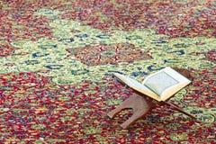 El libro sagrado de musulmanes, el Quran del Islam, se coloca en un de madera fotografía de archivo libre de regalías