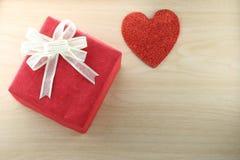 El libro vacío y la caja de regalo roja colocan cerca de forma del corazón en el de madera Foto de archivo