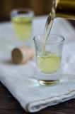 El licor de Limoncello se vierte en un vidrio Fotos de archivo