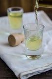 El licor de Limoncello se vierte en un vidrio Fotografía de archivo