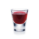 El licor rojo de las bayas es el vaso de medida aislado en blanco. Imagen de archivo
