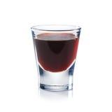 El licor rojo de las bayas es el vaso de medida aislado en blanco. Imagenes de archivo