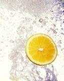 El limón cayó en el agua Foto de archivo