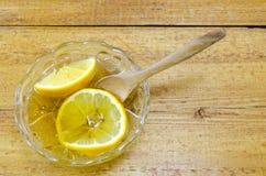 El limón cortado en una placa de cristal llenó de la miel Imagenes de archivo