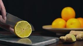 El limón es cortado por el cuchillo afilado en el tablero de la roca, las rebanadas de naranja fresca, la fruta y las vitaminas,  almacen de video