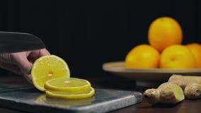 El limón es cortado por el cuchillo afilado en el tablero de la roca, las rebanadas de naranja fresca, la fruta y las vitaminas,  almacen de metraje de vídeo