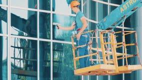 El limpiador de cristal del trabajador en una elevación hidráulica lava la ventana almacen de metraje de vídeo